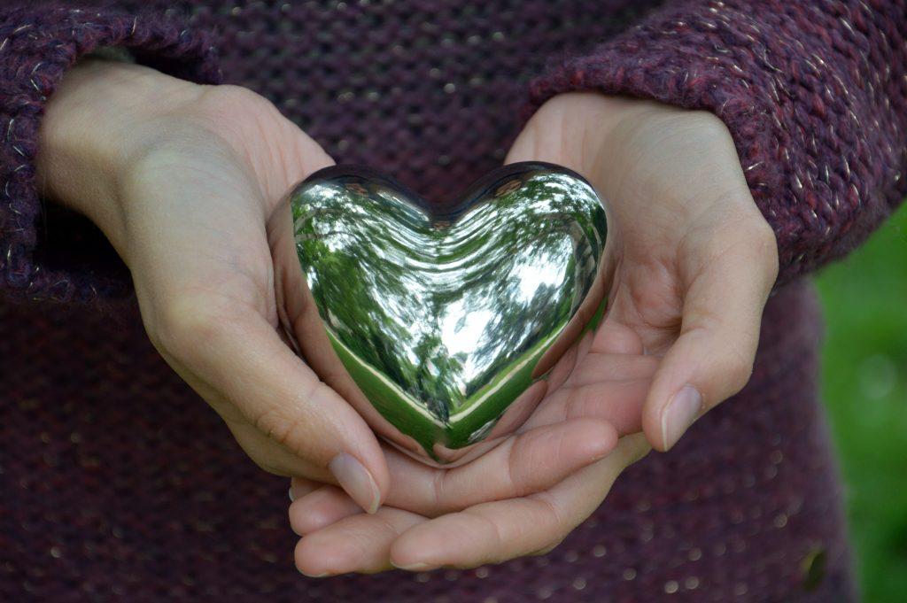 woman's hands show heart