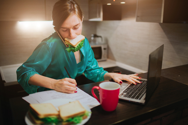 Busy woman eating, drinking coffee, talking on the phone, working on laptop at the same time. Businesswoman doing multiple tasks. Multitasking business person. Freelancer works at night.
