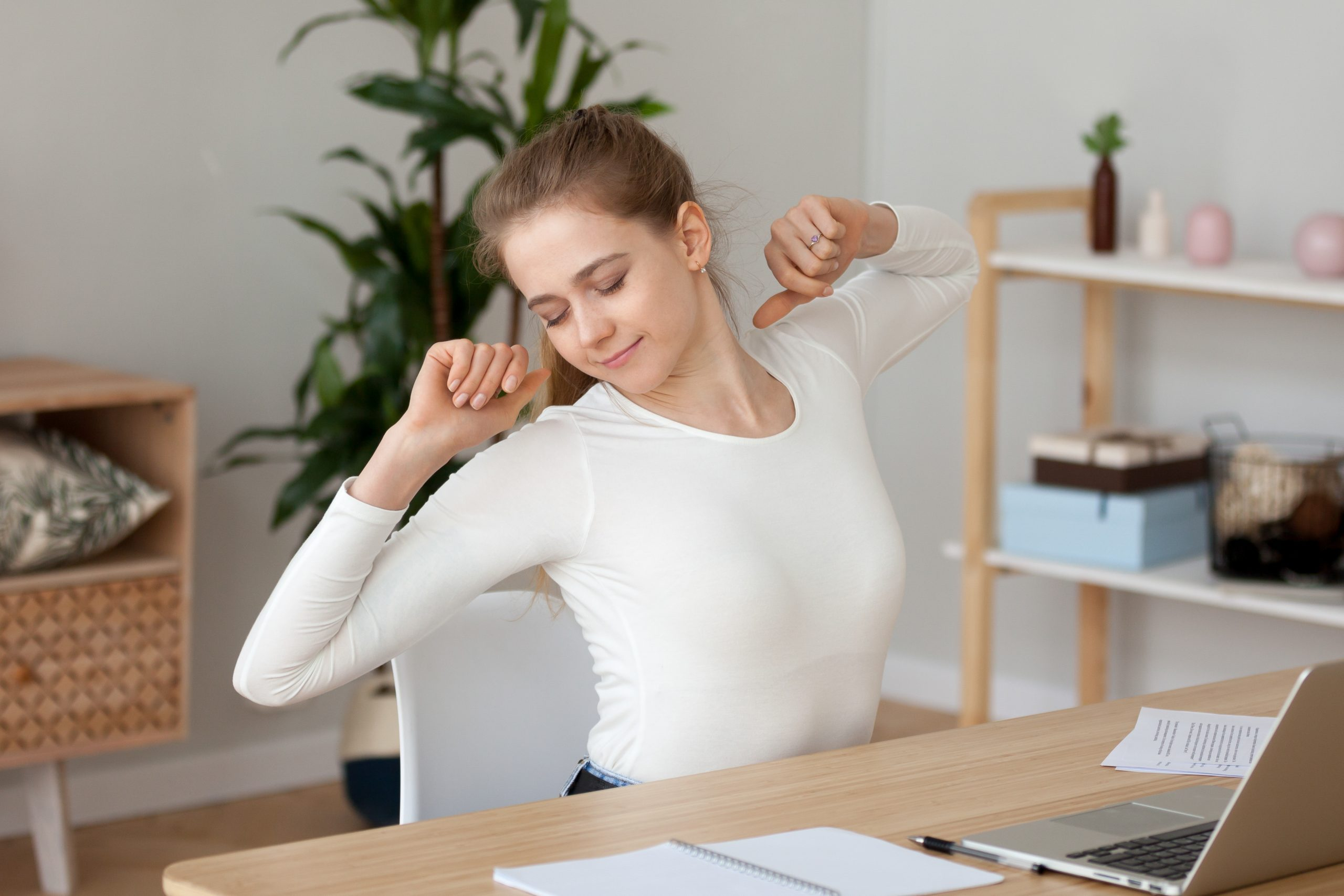 Satisfied young woman stretching, doing exercise with hands behind head in office at workplace, sitting at desk, female employee, student resting, taking break, feeling no stress, relaxing