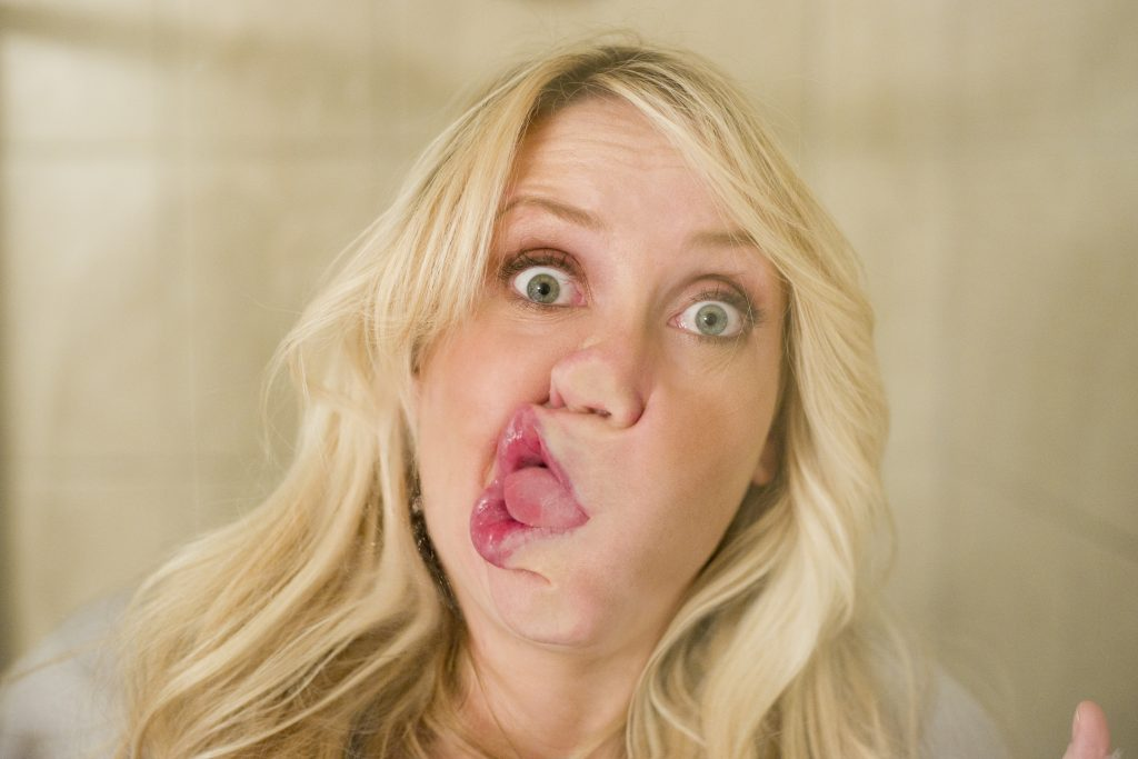 Blonde woman smashing face against window silly look