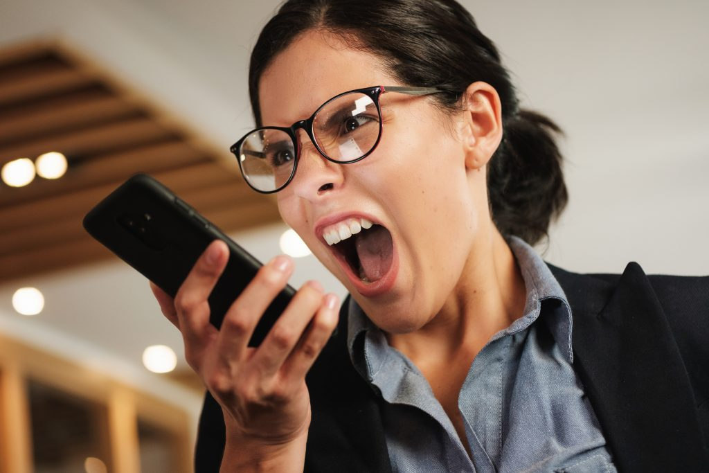 Hysterical Caucasian businesswoman fight on the phone screaming and shouting at the office. Crazy, angry Hispanic executive female professional furious on cell phone call. Anger management work stress