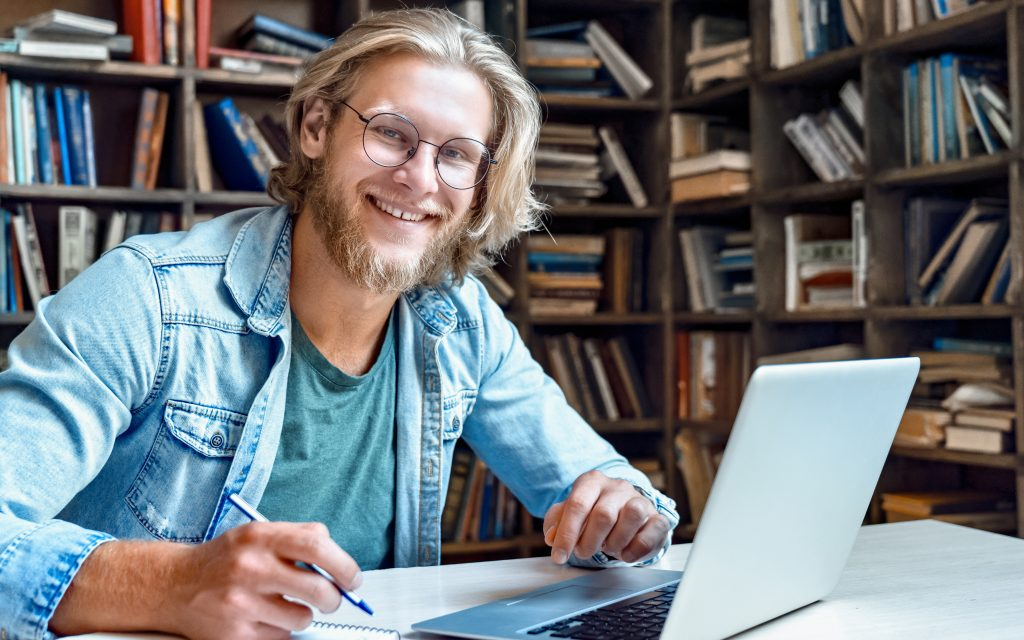 Smiling male student using laptop computer looking at camera learn easy internet course study online e learning in app write notes prepare for test exam with device sit at library desk, portrait.