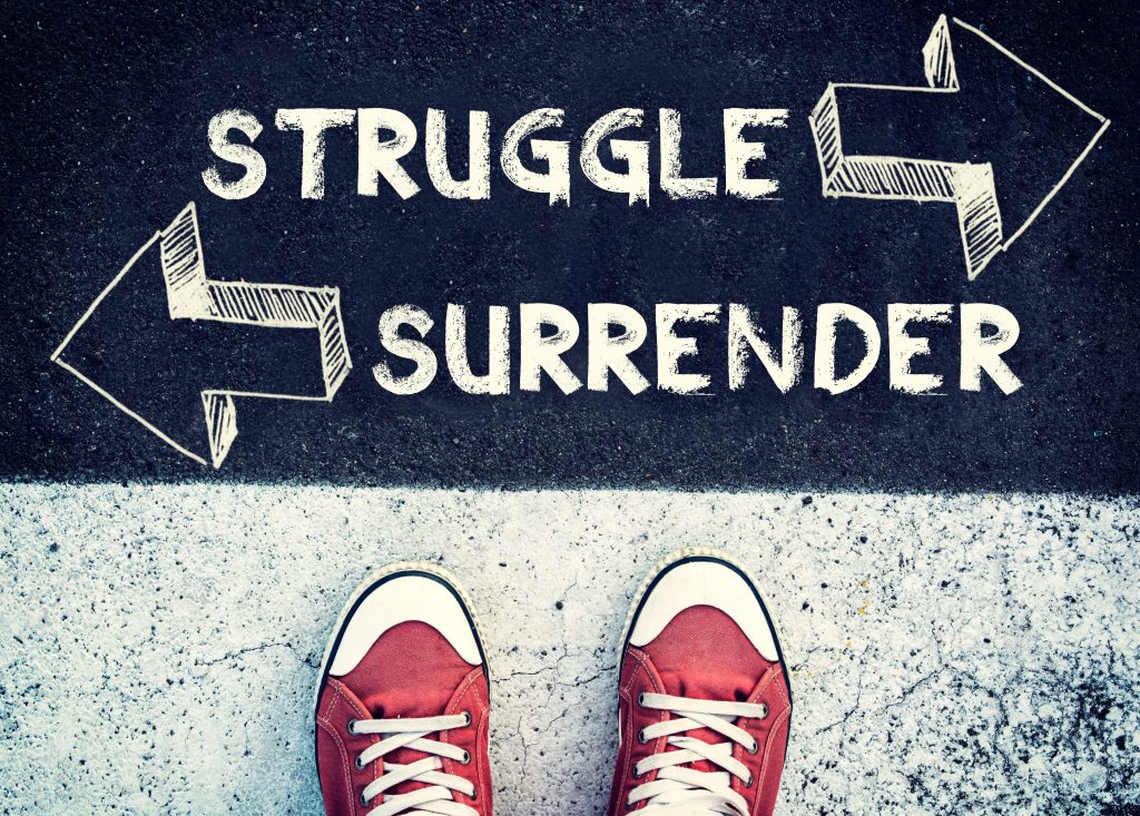 Student standing above the sign surrender and struggle
